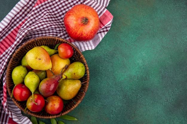 格子縞の布と緑の表面にザクロが付いているバスケットの桃リンゴプラムとして果物のトップビュー