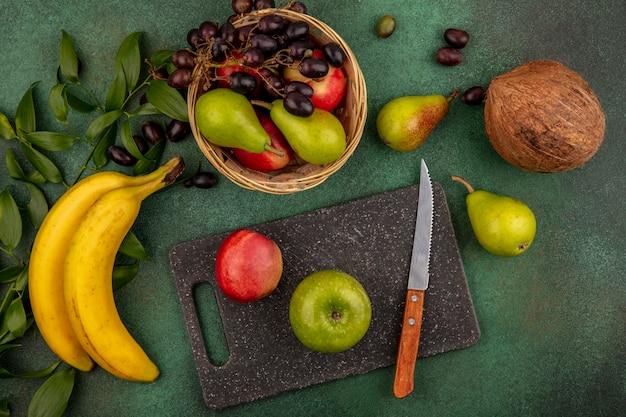 Вид сверху на фрукты в виде персикового яблока с ножом на разделочной доске и груши, кокоса, винограда, банана с листьями на зеленом фоне