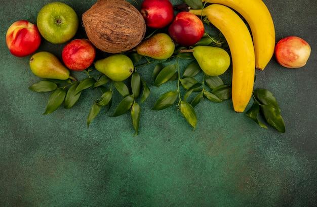 Вид сверху на фрукты как персик, кокос, яблоко, груша, банан с листьями на зеленом фоне с копией пространства
