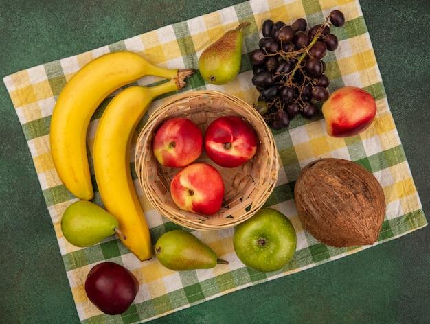 녹색 배경에 격자 무늬 천에 바구니와 포도 배 바나나 코코넛 복숭아로 과일의 상위 뷰
