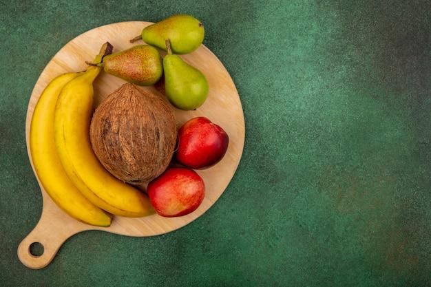 복사 공간 녹색 배경에 커팅 보드에 복숭아 배 코코넛 바나나로 과일의 상위 뷰