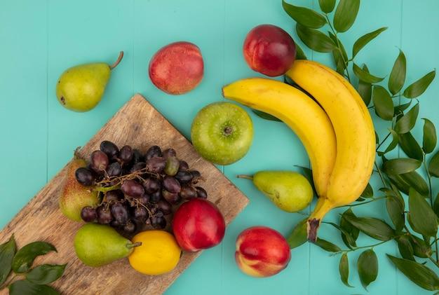 Вид сверху на фрукты как персик, груша, лимон, виноград на разделочной доске с яблоком, бананом и листьями на синем фоне