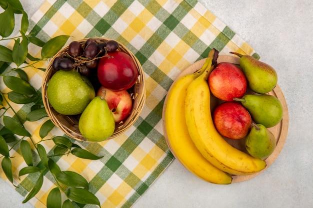 Вид сверху на фрукты, такие как груша, яблоко, персик, виноград, банан в корзине и на разделочной доске с листьями на клетчатой ткани и белом фоне
