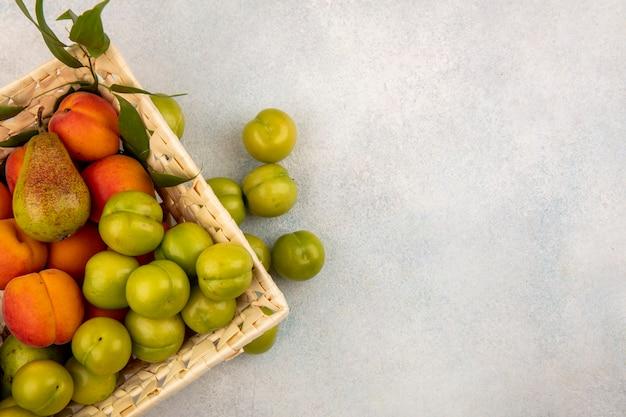 バスケットとコピースペースと白い背景の上の梨アプリコットプラムとして果物の上面図
