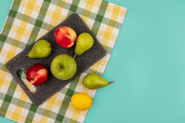 コピースペースと青い背景の上の格子縞の布にレモンとまな板の上の梨桃リンゴとして果物の上面図