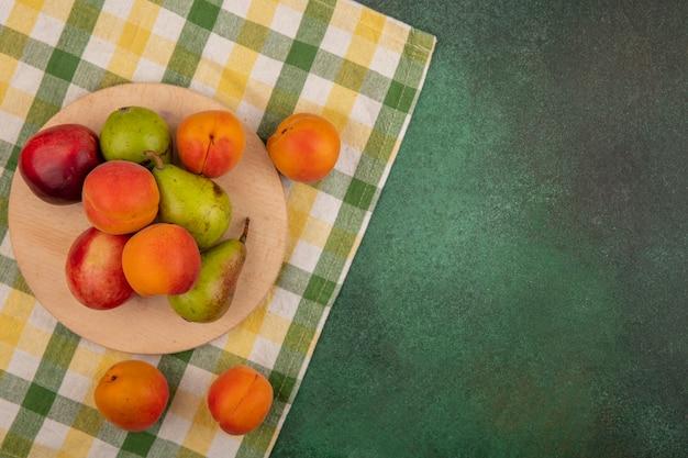 まな板とコピースペースと緑の背景の上の格子縞の布に梨桃アプリコットとして果物の上面図