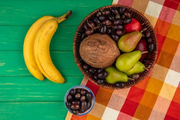 녹색 배경에 격자 무늬 천과 바나나에 바구니에 배 복숭아 포도 코코넛으로 과일의 상위 뷰