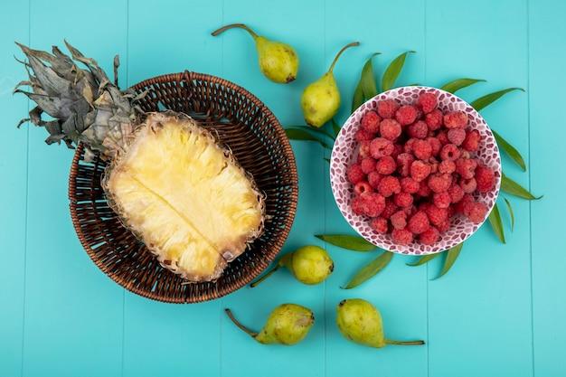 Вид сверху на фрукты в виде половины ананаса в корзине и миске малины с персиками и листьями на синей поверхности