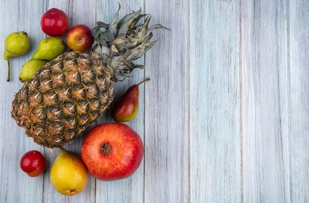 木の表面にパイナップルピーチプラムザクロとして果物のトップビュー