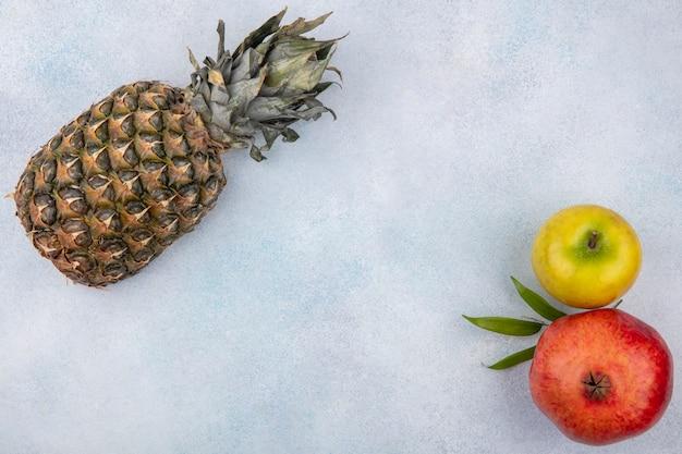 Вид сверху на фрукты, такие как ананас, гранат и яблоко на белой поверхности