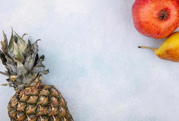 コピースペースを持つ白い表面上のパイナップル、ザクロ、桃として果物のトップビュー