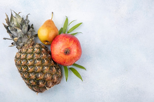 Вид сверху на фрукты, такие как ананас, гранат и персик на белой поверхности с копией пространства