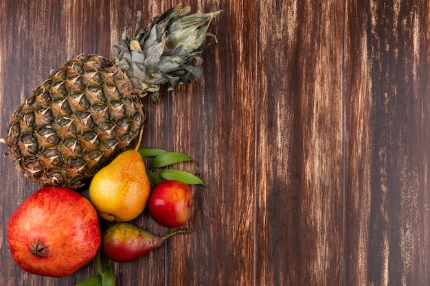 Вид сверху на фрукты, такие как ананас, гранат и персик на деревянной поверхности с копией пространства