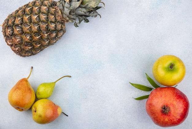 Вид сверху на фрукты, такие как ананас, гранат, яблоко, груши и персик на белой поверхности