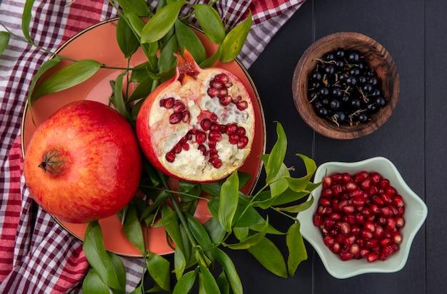 格子縞の布の上の葉と黒の表面にスローとザクロ果実のボウルとザクロの半分と全体のプレートとして果物の上面図