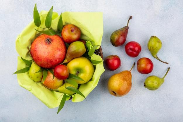 白い表面上のバスケットに梅リンゴ桃とザクロとして果物のトップビュー