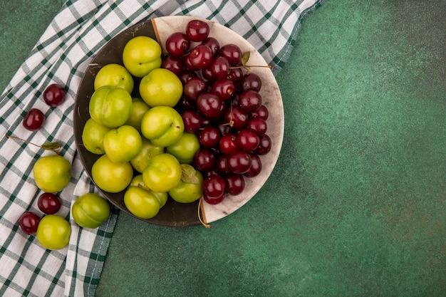 복사 공간이 녹색 배경에 접시와 격자 무늬 천에 자두와 체리로 과일의 상위 뷰