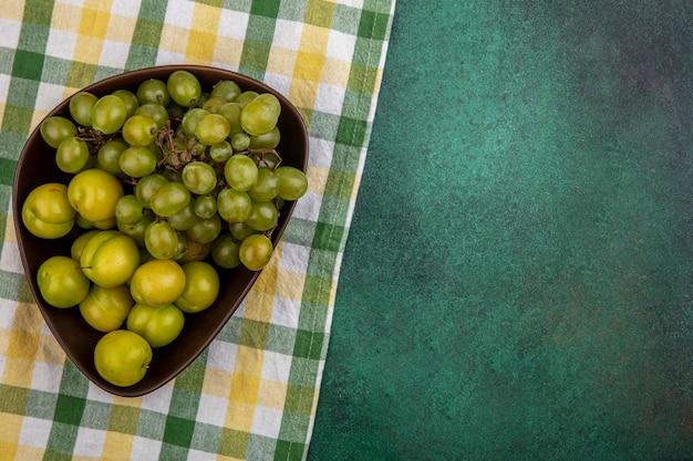 Вид сверху на фрукты в виде слив и винограда в миске на клетчатой ткани и зеленом фоне с копией пространства