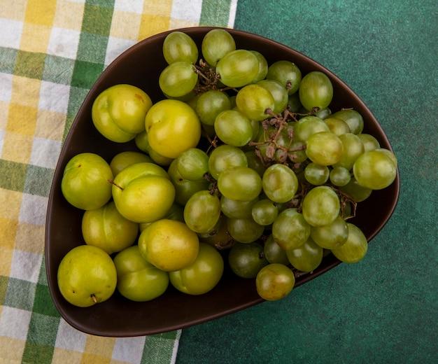 격자 무늬 천과 녹색 배경에 그릇에 자두와 포도로 과일의 상위 뷰