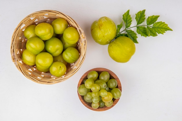 바구니에 자두와 흰색 배경에 흰색 포도 열매의 그릇과 녹색 pluots로 과일의 상위 뷰