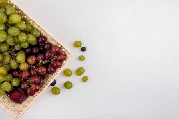コピースペースと白い背景の上のバスケットとブドウの果実のプルオットとブドウとしての果物の上面図