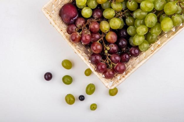 白い背景の上のバスケットとブドウの果実のプルオットとブドウとしての果物の上面図