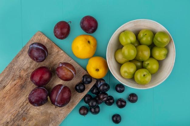 Вид сверху фруктов в виде плюотов и виноградных ягод на разделочной доске с нектакотами и миской слив и виноградных ягод на синем фоне