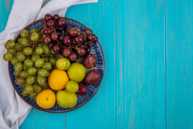 コピースペースと青い背景の上の白い布の上のプレートのプルオットネクタコットプラムとブドウとしての果物の上面図