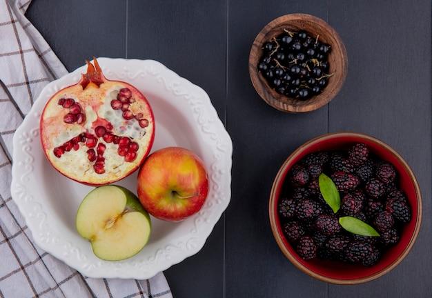 格子縞の布のプレートに丸ごとリンゴと黒の表面にスローとブラックベリーのボウルとザクロとリンゴの半分として果物のトップビュー