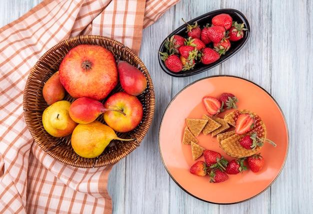 Вид сверху на фрукты в виде граната, персика и яблока в корзине на клетчатой ткани с пластинами вафельного печенья и клубники на деревянной поверхности