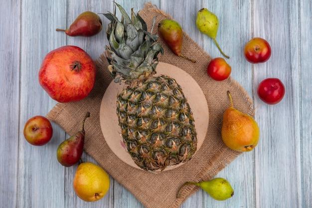 Вид сверху на фрукты как гранат, персик, сливы и ананас на разделочной доске на мешковине на деревянной поверхности