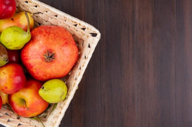 コピースペースを持つ木製の表面のバスケットにザクロ桃梅リンゴとして果物のトップビュー