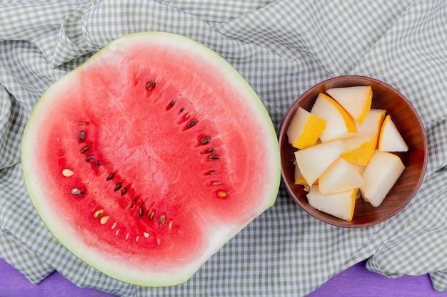 半分のスイカと格子縞の布と紫色の背景にスライスしたメロンのボウルとして果物のトップビュー