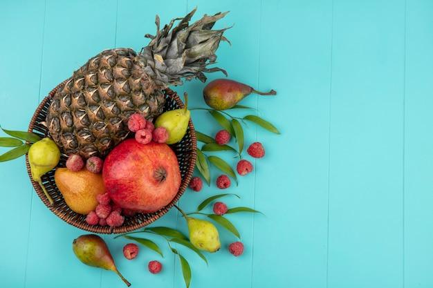 青い表面に葉が付いているバスケットの果物のトップビュー