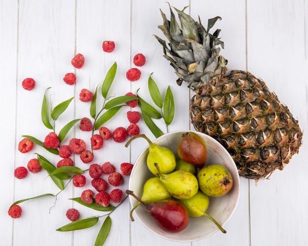Вид сверху на фрукты в миске с листьями на деревянной поверхности
