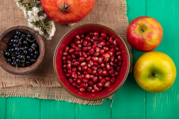 Вид сверху на фрукты в мисках с цветком граната на мешковине и яблоками на зеленой поверхности