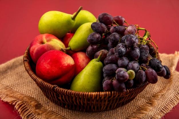 赤い背景の上の袋の布の上の木製のボウルにグレープ梨桃のような果物の上面図