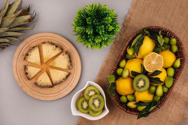 灰色の背景に木製のキッチンボードにパイナップルスライスとボウルにキウイスライスと袋布のバケツにキウイキンカンとレモンなどの果物の上面図