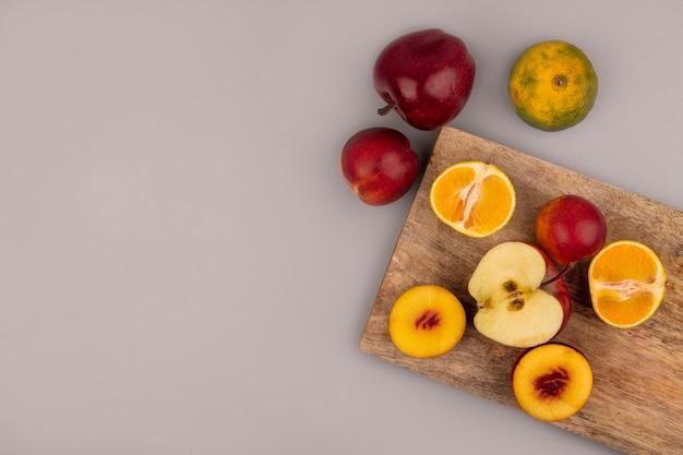 Вид сверху на фрукты, такие как персики, яблоки и мандарины, изолированные на деревянной кухонной доске на серой стене с копией пространства