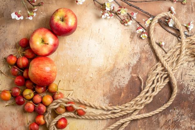 Вид сверху на фрукты, аппетитные три яблока и ветви вишневого дерева