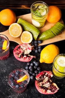 暗い木製の背景にデトックス水とグラスの横にある果物、野菜、ベリーの上面図