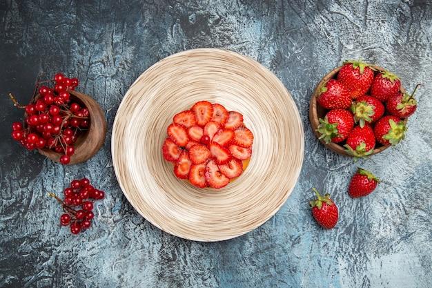 暗い表面に新鮮なイチゴとフルーティーなケーキの上面図