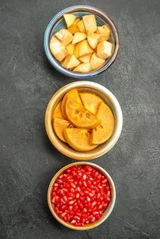 ダークグレーの机の上に新鮮なスライスフルーツとフルーティーサラダの上面図