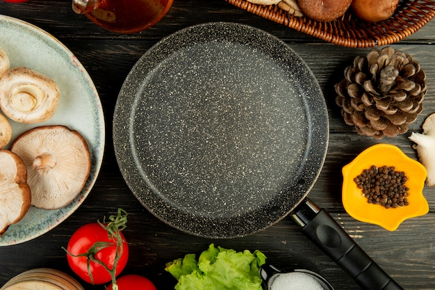 Вид сверху сковороды и свежие грибы с помидорами шишки черный перец, расположенных вокруг на черном дереве
