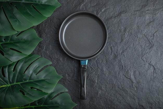 Вид сверху сковороды на черном фоне с зелеными листьями.
