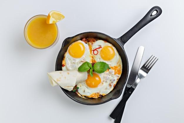 Вид сверху на сковороду с тремя яичницами