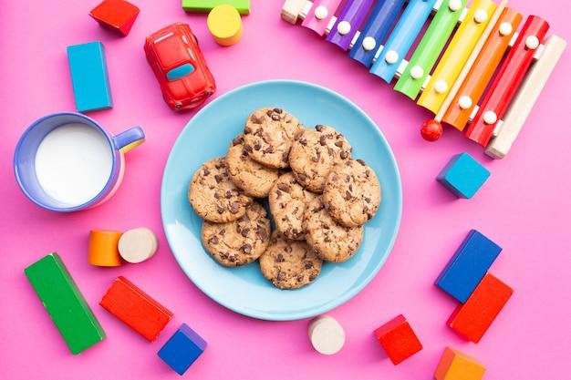 ピンクの背景におもちゃと着色された木琴を伴うミルクとビスケットのクッキーと面白い子供の朝食のトップビュー