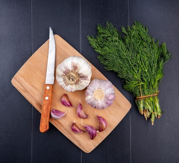Вид сверху луковицы чеснока и зубчиков с ножом на разделочной доске и пучком укропа на черной поверхности