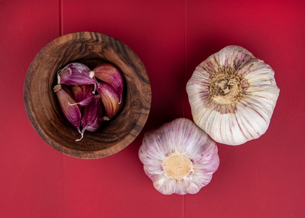 Вид сверху чеснока в миске и луковиц чеснока на красной поверхности