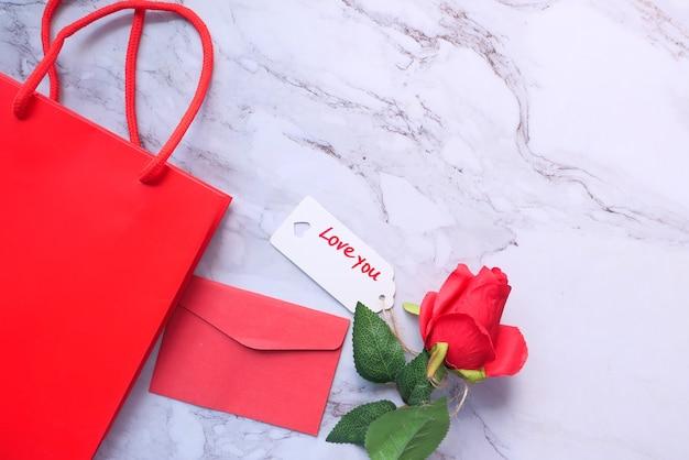 白い背景の上のギフトボックス、封筒、バラの花の上面図。